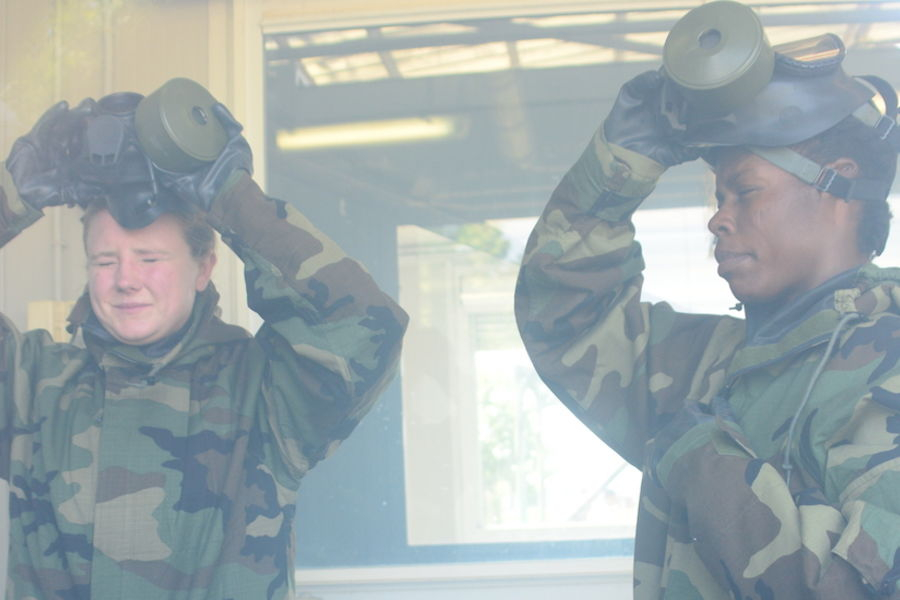 Military personnel in camouflage put on ventilator masks before an exercise involving airborne toxins