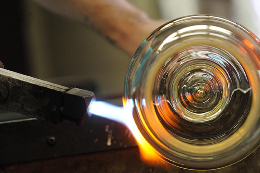 Glassblowing process, flame being held to glass bubble on blowpipe