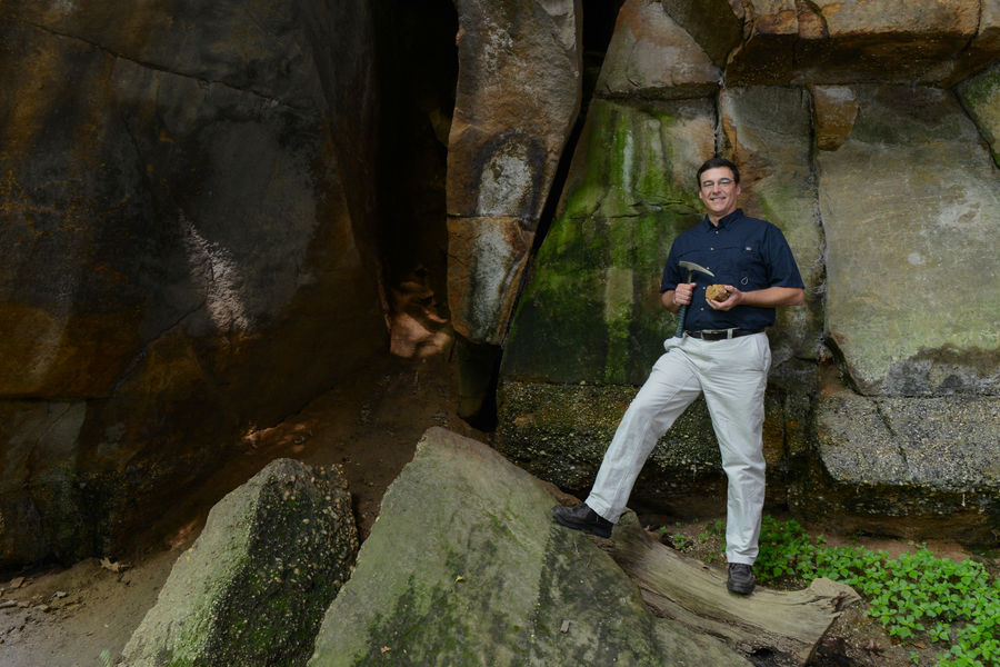 David Hacker, associate professor of geology at Kent State University at Trumbull, poses for a photo near a rock outcropping in the Gorge Metro Park in Summit County. Hacker has been selected as Kent State's Scholar of the Month.