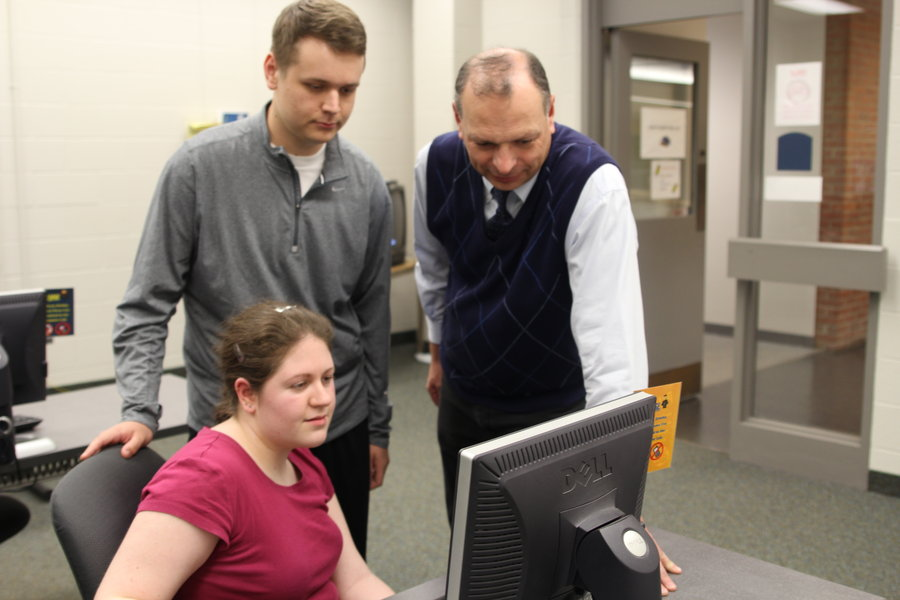 oseph Kuvshinikov (right), associate professor at Kent State Ashtabula, works with Kent State Ashtabula students senior business management major Jennifer Bean and senior insurance studies major Callen Weber.