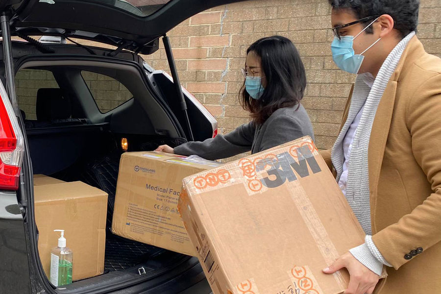 Irvin Cardenas and Yuqiao Xu load donated safety supplies that they delivered to Summa Health in Akron.