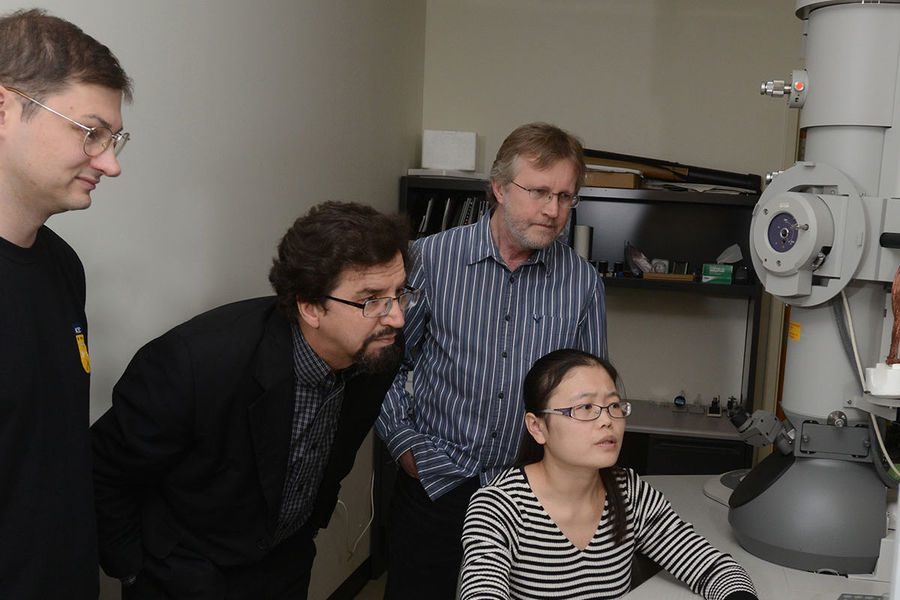 Oleg Lavrentovich, Ph.D. (second from left), works in a microscopy lab with a colleague and Kent State students.