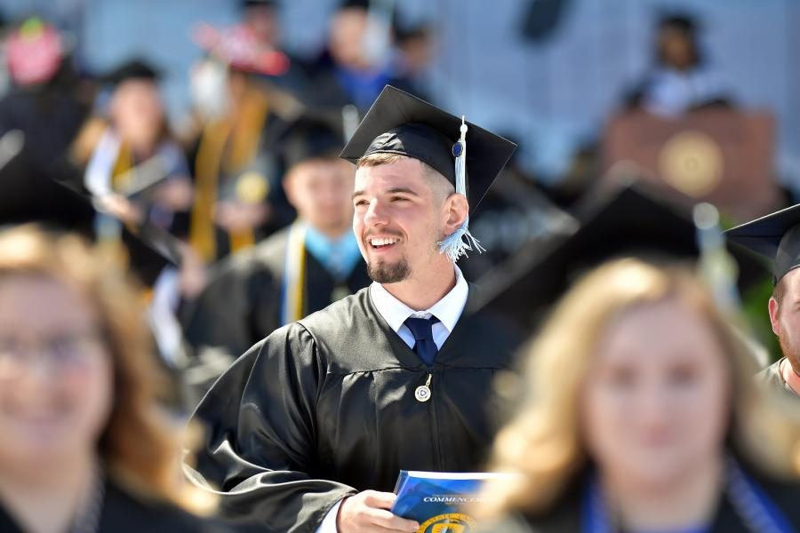 A new Kent State University graduate smiles during his commencement ceremony.