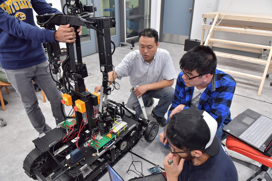 """Dr. Jong-Hoon Kim, Ph.D. assistant professor of Computer Science, and his students in the ATR Lab assembling their robot, """"Telebot-2"""" in preparation for their trip to Tokyo."""