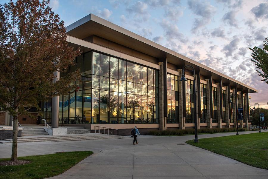 A beautiful sunset is reflected off the glass window of the ISB Building on Kent Campus.
