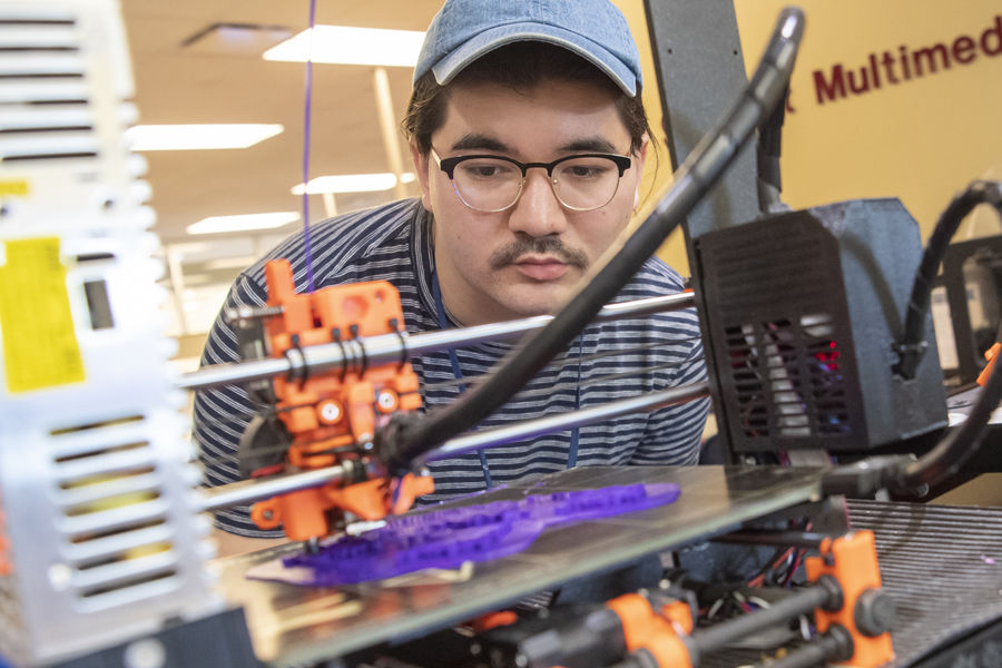 Nick Lee, junior painting major, produces a class assignment on a 3D printer in the Student Multimedia Studio