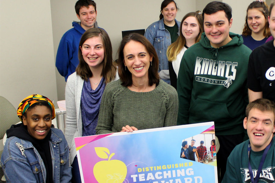 Jacqueline Marino smiles with her students after winning the 2019 Distinguished Teaching Award.