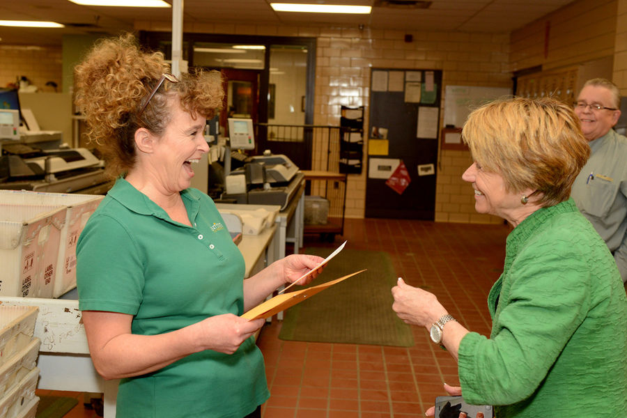 April Miller reacts as Kent State President Beverly Warren visits her in the mailroom and tells her she has won a President's Excellence Award.