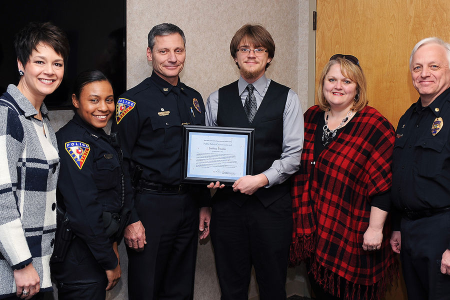 Members of Kent State's Division of Student Affairs and Department of Public Safety pose for a photo with Kent State student Josh Paulin and his mother (fourth and fifth from left) during the presentation of the Public Safety Citizen's Award.