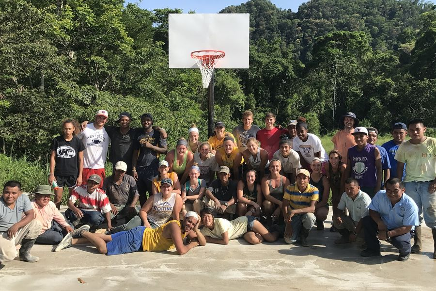 The Kent State Golden Flashes pose with members of the community on the multipurpose court they constructed in Aguacate, Belize.