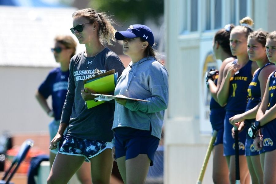 Kent State field hockey coach Kyle DeSandes-Moyer (wearing hat) stands with her players and assistant coaches.