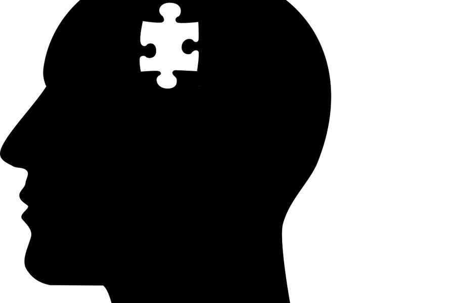 Image of a silhouette with a missing puzzle piece in the mind and a hand holding it.