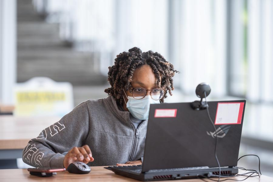 A student peers at her laptop while on Kent Campus.