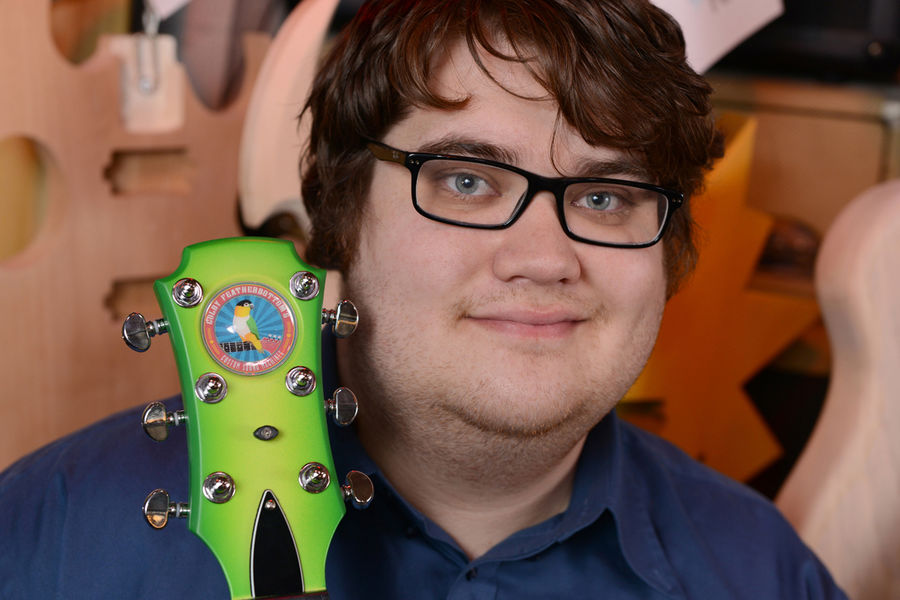 Kent State student Ryan Schoeneman poses with a nearly complete guitar in his workshop.