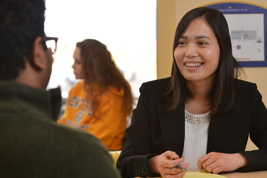 Xiaoling Pu, associate professor of finance in Kent State's College of Business Administration, works with a student in the Business Administration Building.