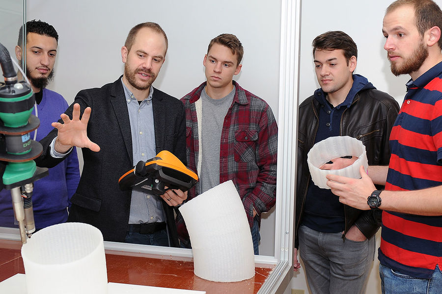 Brian Peters, assistant professor in Kent State's College of Architecture and Environmental Design, reviews the use of 3D printing technology with his class.