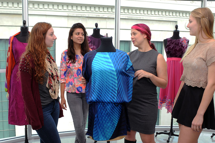 September Scholar of the Month Margarita Benitez (second from right) analyzes a garment with her students in the School of Fashion Design and Merchandising, in Rockwell Hall.