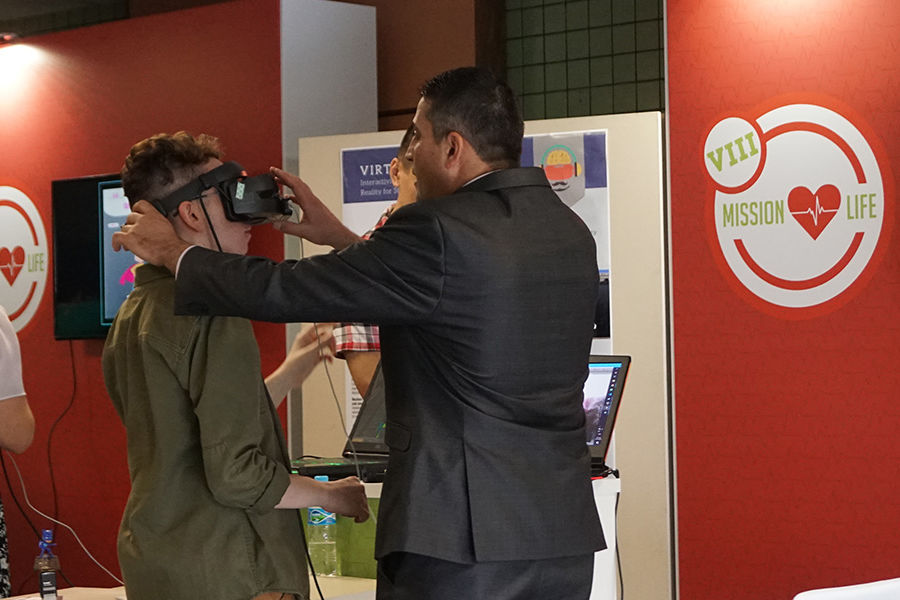 Shadi Kanan (right) assists a student to put on the Virtual Harmony device.