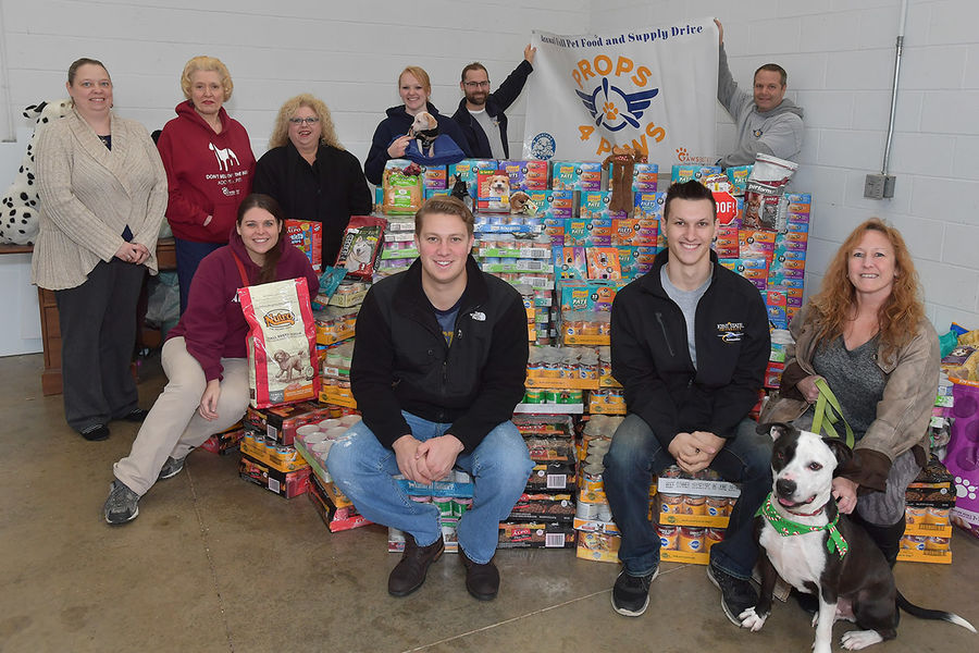 The Kent State University Airport employees gather around donations from their fifth annual Props-4-Paws collection event this fall