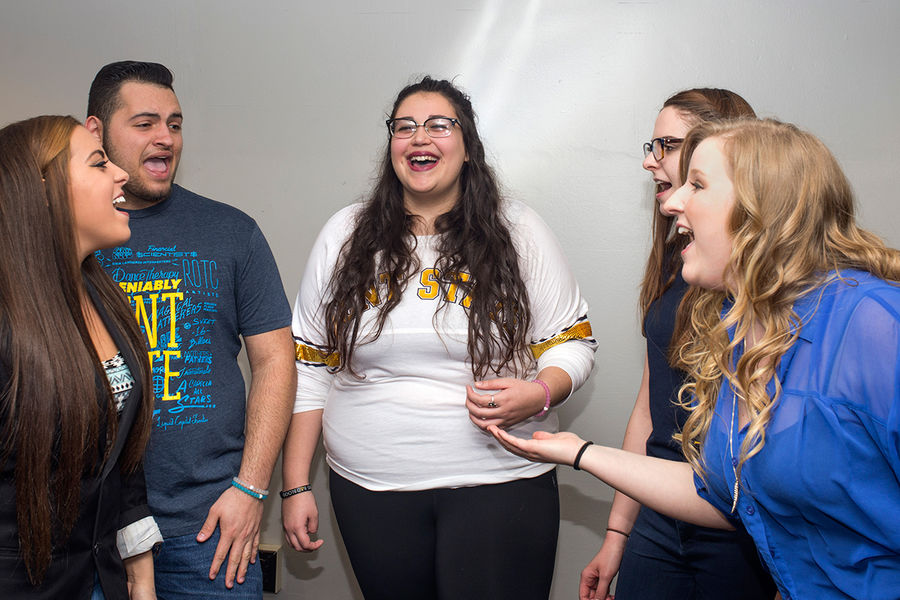 Members of the Vocal Intensity a cappella singing group practice in a lounge in Tri-Towers.