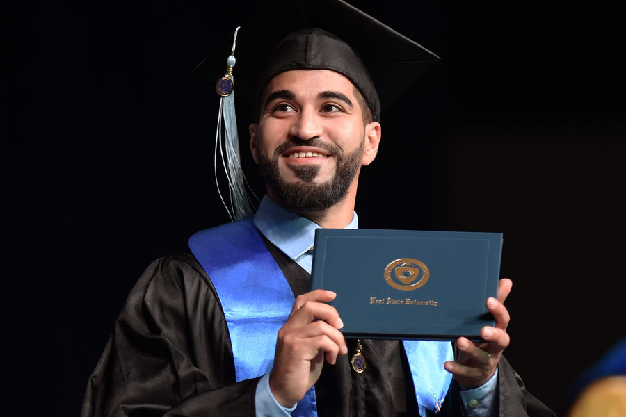 A Kent State University graduate displays his diploma for family and friends during the baccalaureate degree ceremony at the Memorial Athletic and Convocation Center.
