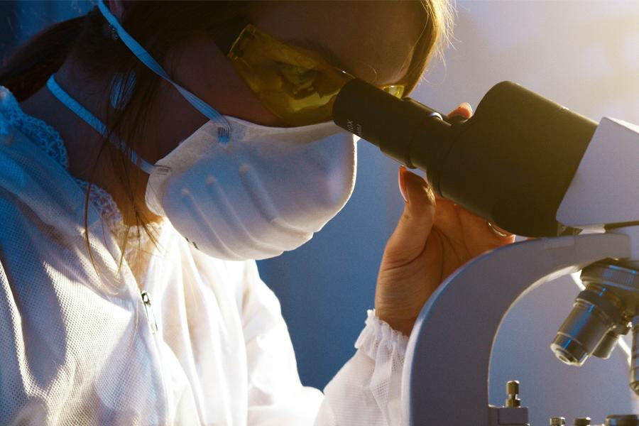 A scientist looking through a microscope