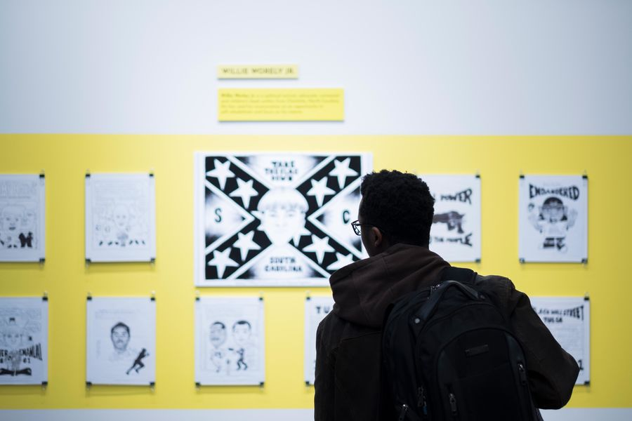 A student looks through artwork included in the GONE. exhibit