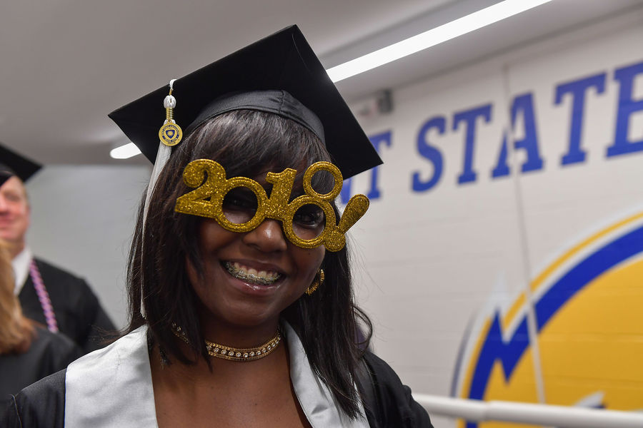 A College of Business Administration graduate show off her glasses while in line to enter Kent State's Memorial Athletic and Convocation (MAC) Center.
