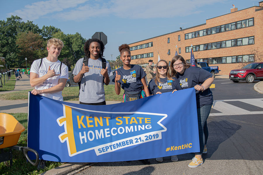 Students carrying the Kent State Homecoming banner in the parade pose for a photo.