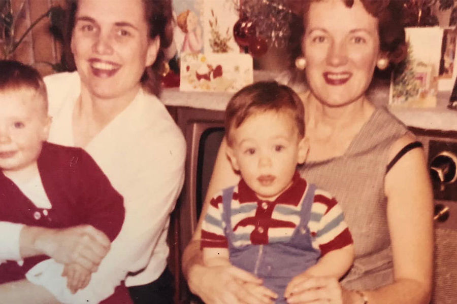 Tom Jennings as a child, sitting on his mother