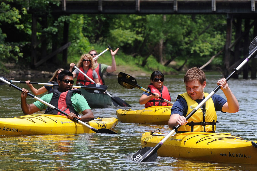 Kent State students paddle their way down the Cuyahoga River near downtown Kent. Kent State's Department of Recreational Services runs Crooked River Adventures, offering kayak, canoe, paddleboard and tubing trips during the summer months.