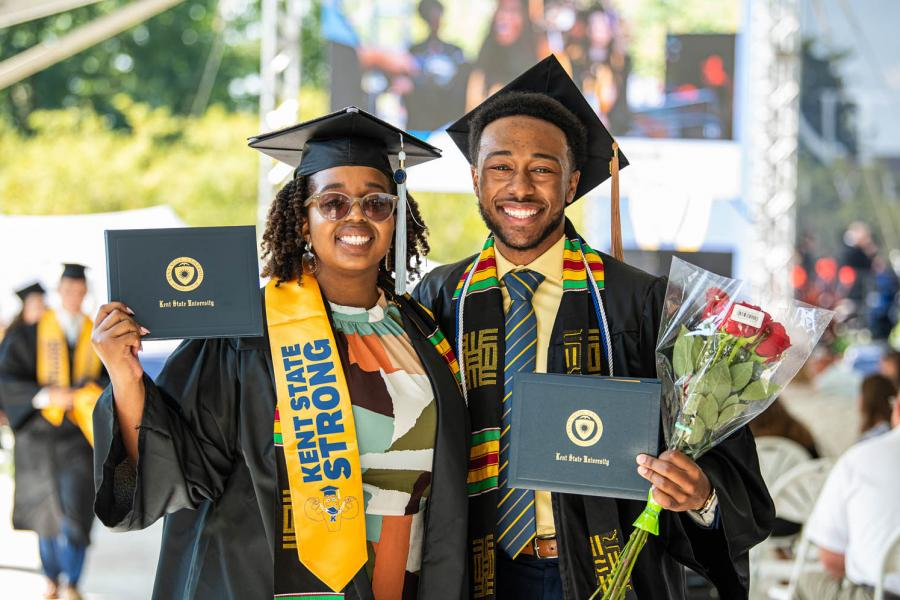 New Kent State graduates smile while holding their degrees after their commencement ceremony.