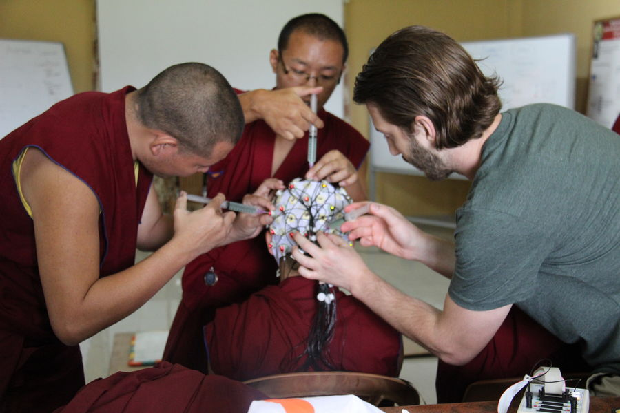 Kent State researchers use EEG caps to study the brain activity of monks during a debate.