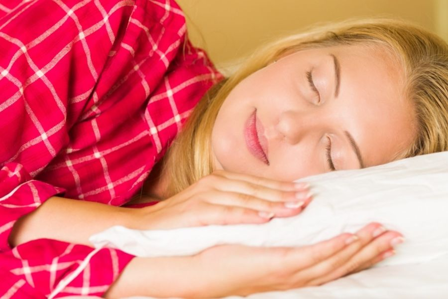 Stock photo of a blonde woman in red pajamas sleeping
