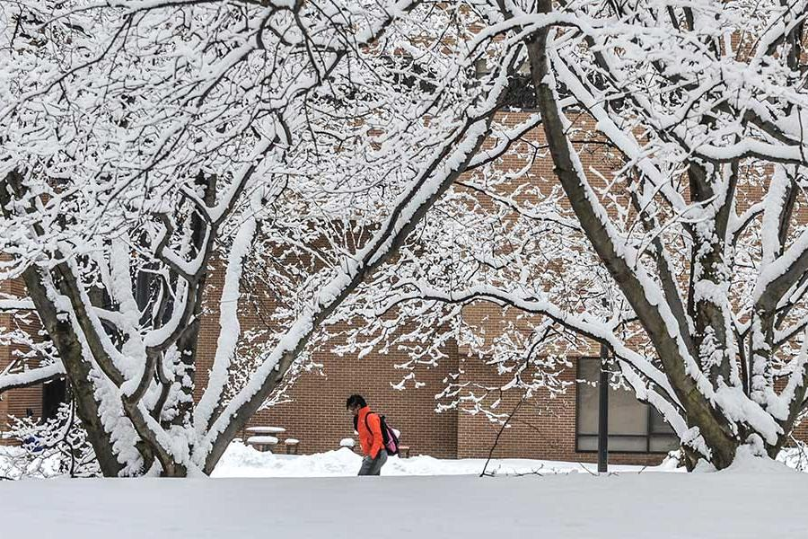 A passing student adds bright color to a snowy scene behind Henderson Hall on the Kent campus.