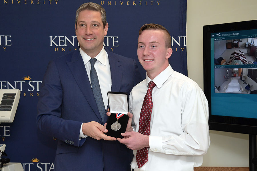 Congressman Tim Ryan displays The Congressional Award Silver Medal, presented to Kent State University nursing student Austin Croft in Henderson Hall, home of the College of Nursing.