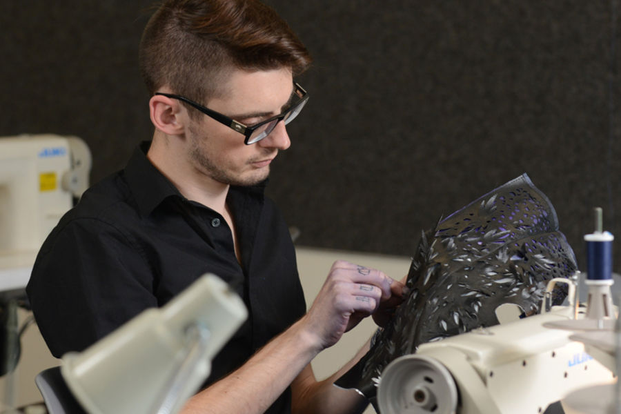 Will Riddle works on his Supima collection in the Kent Fashion Design Studio in 2013. (Photo by Bob Christy, Kent State University)