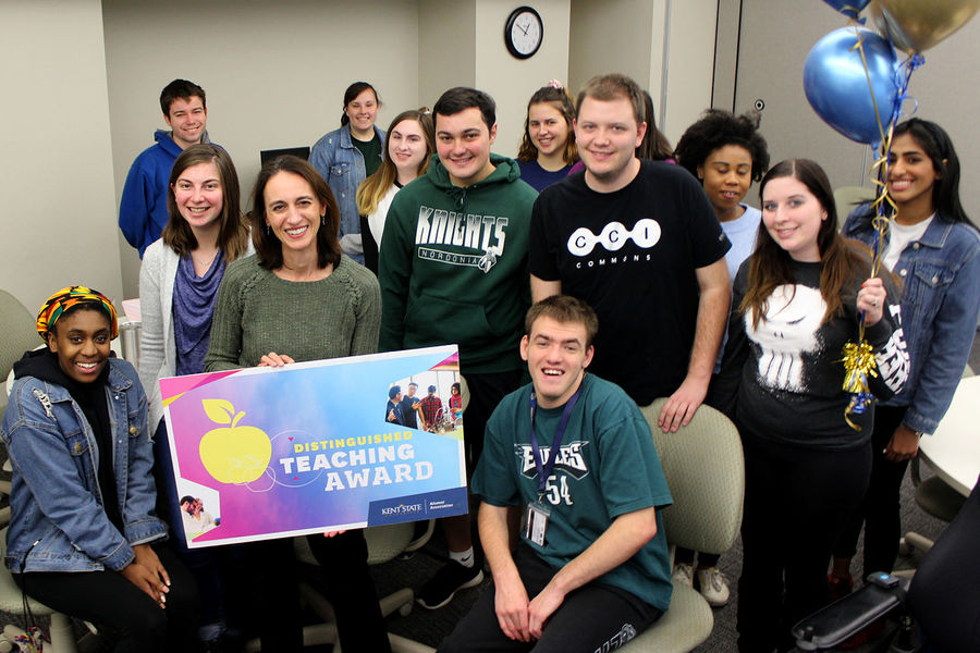 Jacqueline Marino, smiling and posed with students