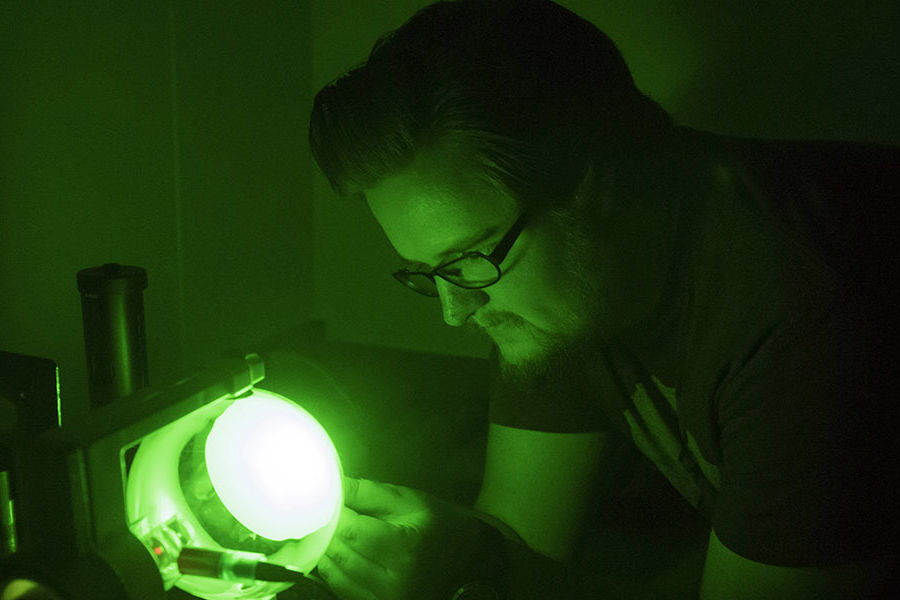 An undergraduate student uses a device to measure light refraction in a Smith Hall physics lab.