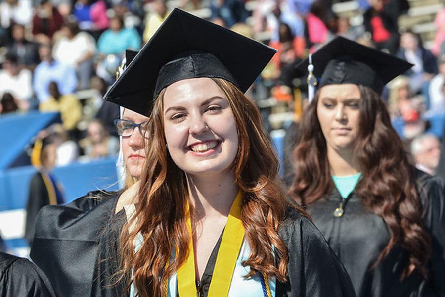 Graduating students walk at Dix Stadium during Kent State University's One University Commencement.