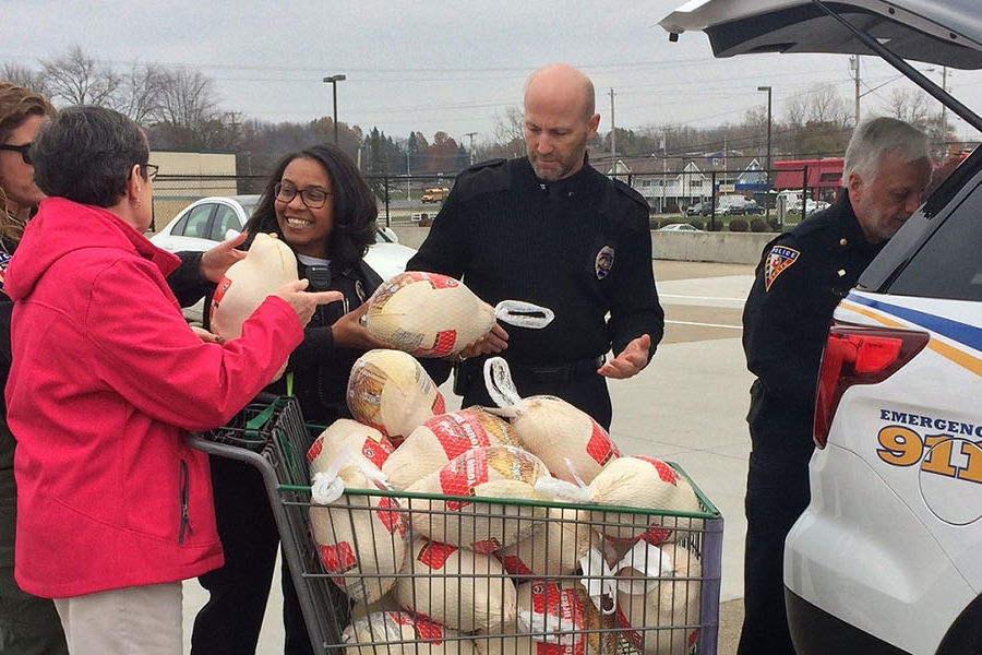 Members of Kent State Police Services load frozen turkeys for Kent Social Services into a police vehicle.