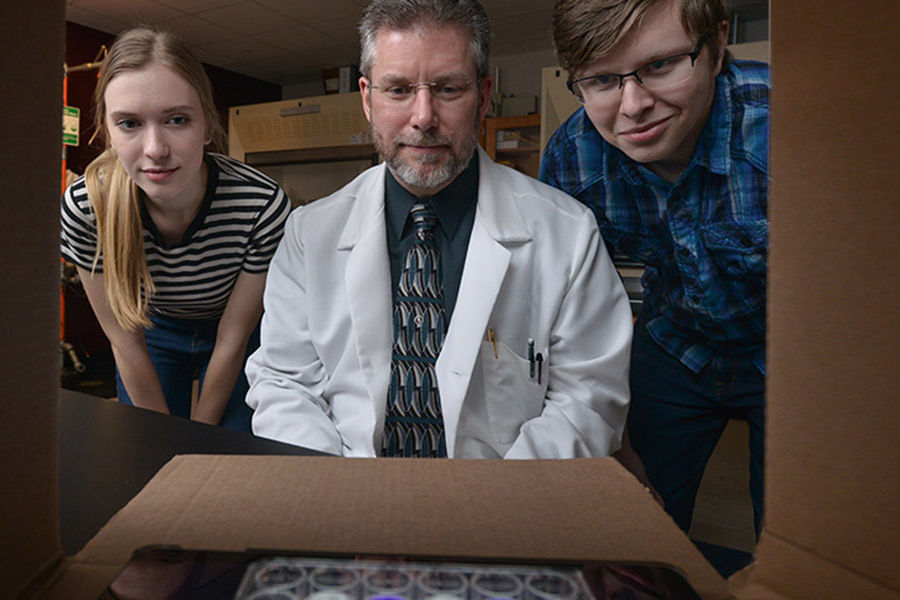 Kent State University at Tuscarawas chemistry professor Christopher Fenk (center) is striving to provide classrooms with affordable alternatives to lab equipment using cellphones. Post-secondary students Sarah Worrell and Jared Norman also are pictured.