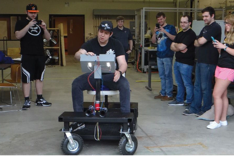 Mechanical and electrical engineering technology students at Kent State University at Tuscarawas test drive an electric cart that they designed and built for their capstone project.
