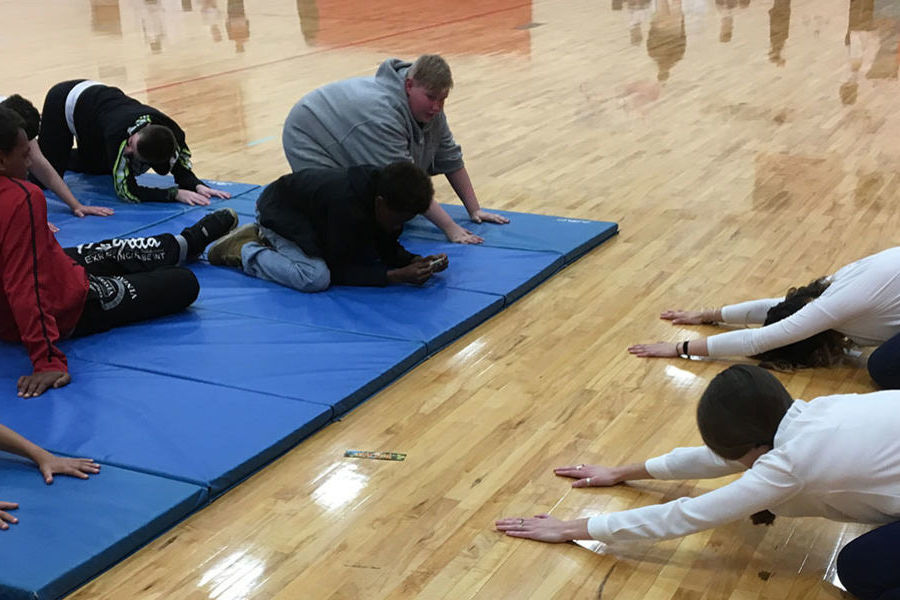Kent State University College of Nursing seniors Anna Hunker and Alyssa Lodi lead a group of middle school students through simple yoga stretches to promote relaxation and mindfulness during the health and wellness fair.