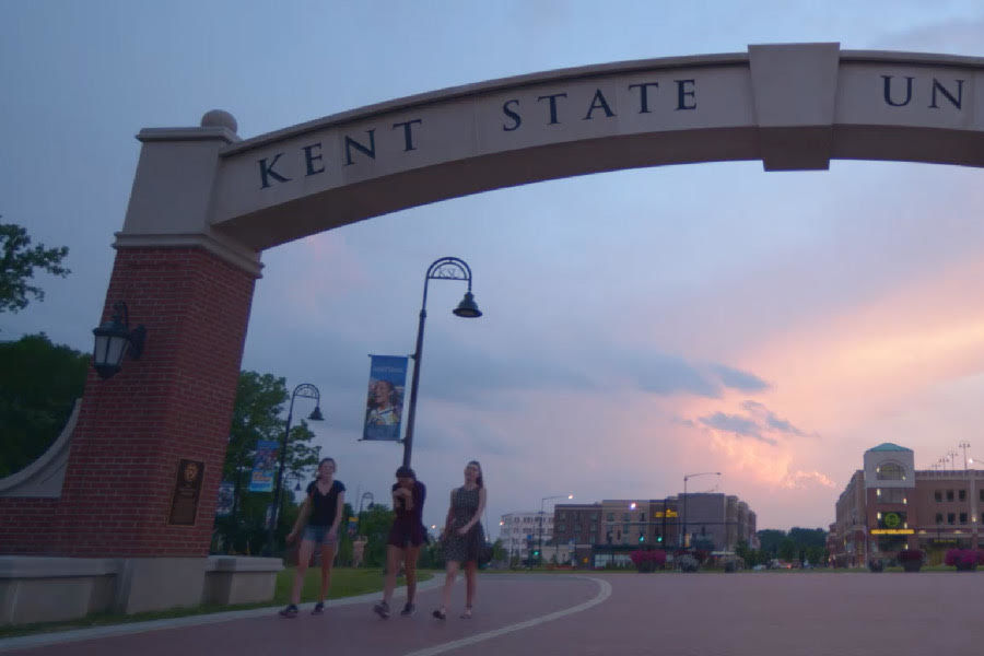 Kent State University students enjoy time together walking under the arch on the Lefton Esplanade at the Kent Campus.
