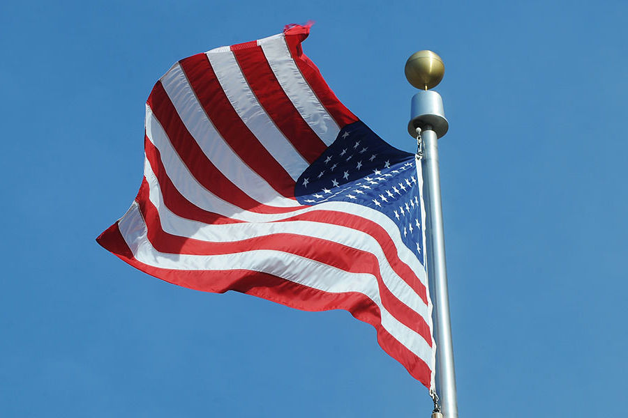 American flag on a flag pole against blue sky