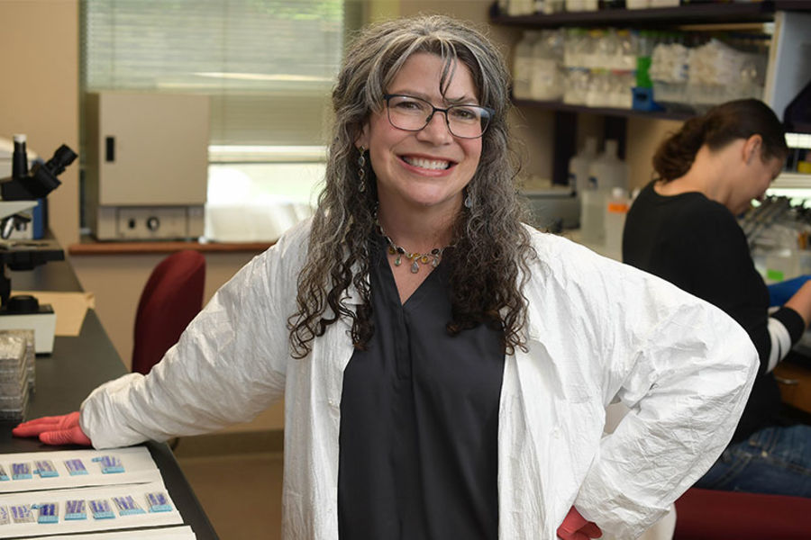 Researcher, posed and smiling for the camera in labcoat