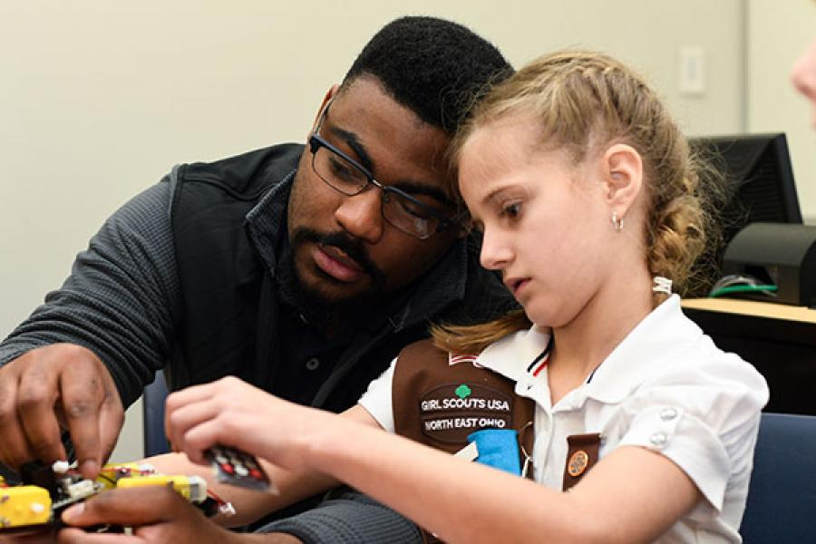 Professor helping a young girl scout with a model plane