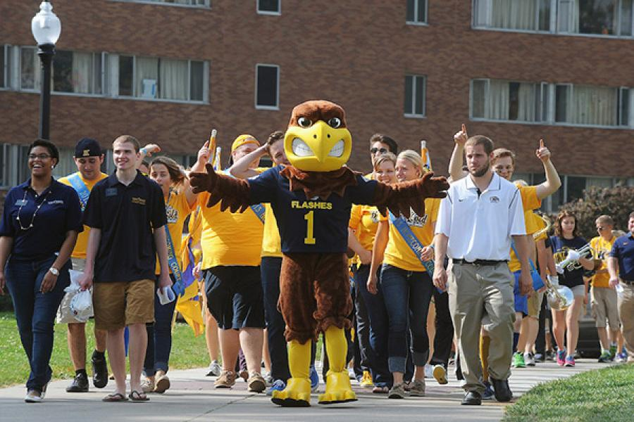 Flash the Kent State mascot leads a group tour on the Kent Campus near the residence halls.