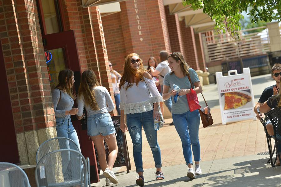 Students walk through the streets of Downtown Kent, talking and laughing near storefronts.